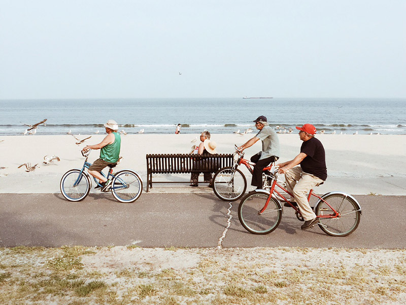 Photo of people riding bikes on a boardwalk of a beach