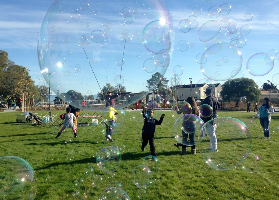 Children play on the grass at Hilltop Park amidst giant soap bubbles