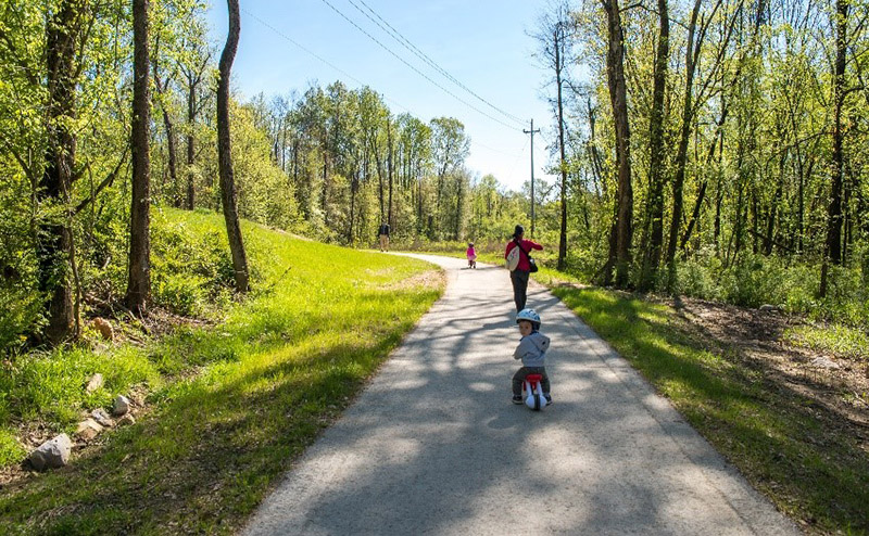 Photo of parents and kids walking on a trail