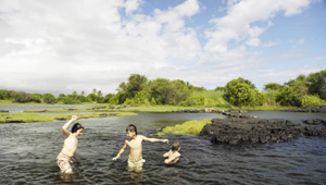 Children splash and play in the fishing ponds at Honu'apo