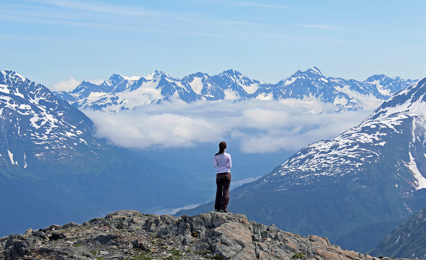 A woman overlooks a mountain range