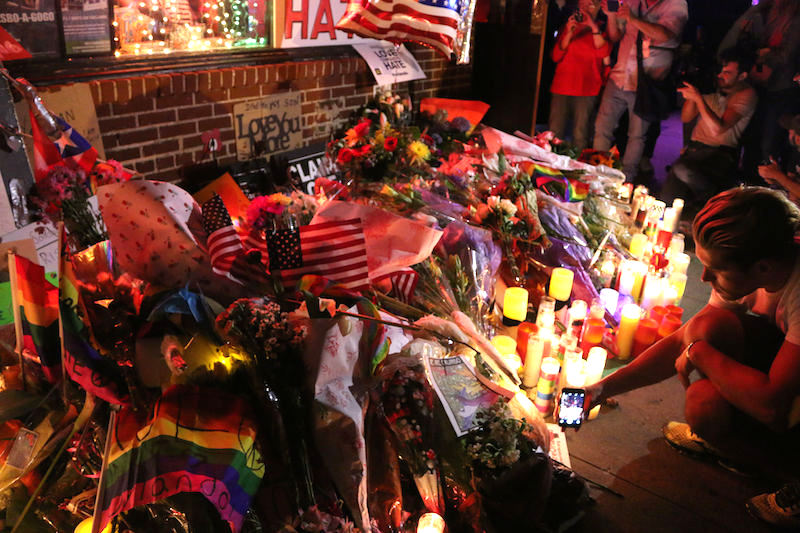 Outside the Stonewall Inn, people take pictures of a memorial for the victims of the Orlando shooting.