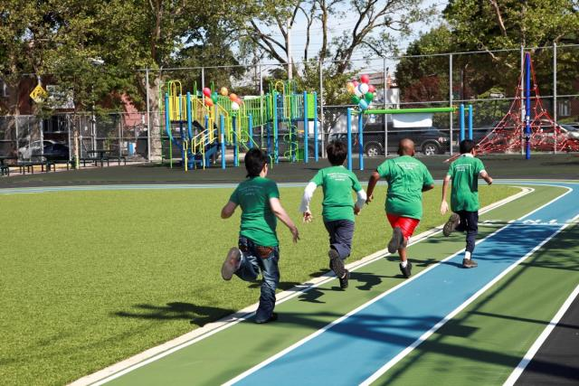 Four school boys run on the new running track at P.S. 33 Community Playground