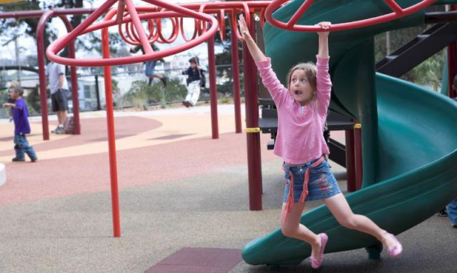 Young girl swings on the playground equipment at Potrero Hill Playground, San Francisco