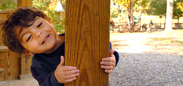 A boy peeks from behind a post on a bandstand in Jake Rusher Park, North Carolina