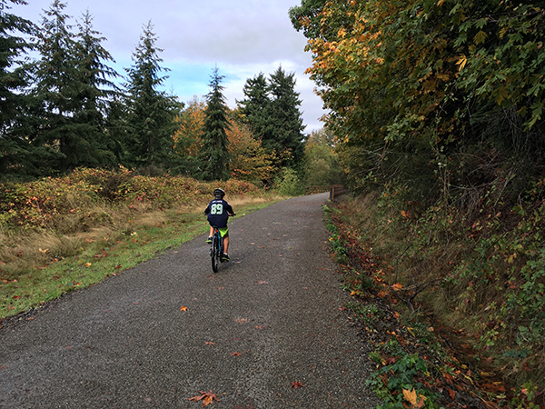 A boy rides his bike along a tree-lined trail