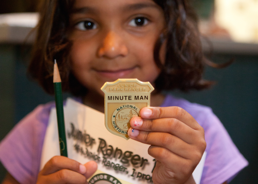 A young girl holds up her Junior Ranger badge.