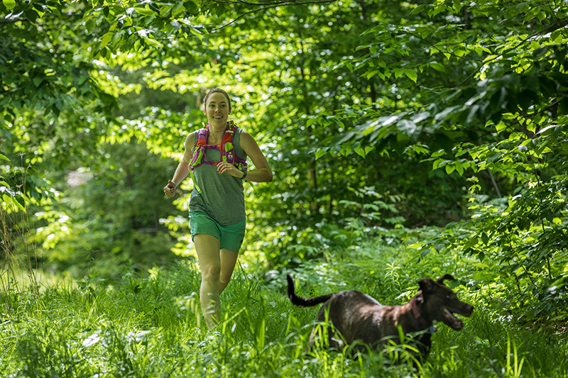 Photo of women running in the forest with her dog