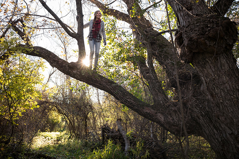 Photo of a woman standing on a tree branch at Elk River in Minnesota