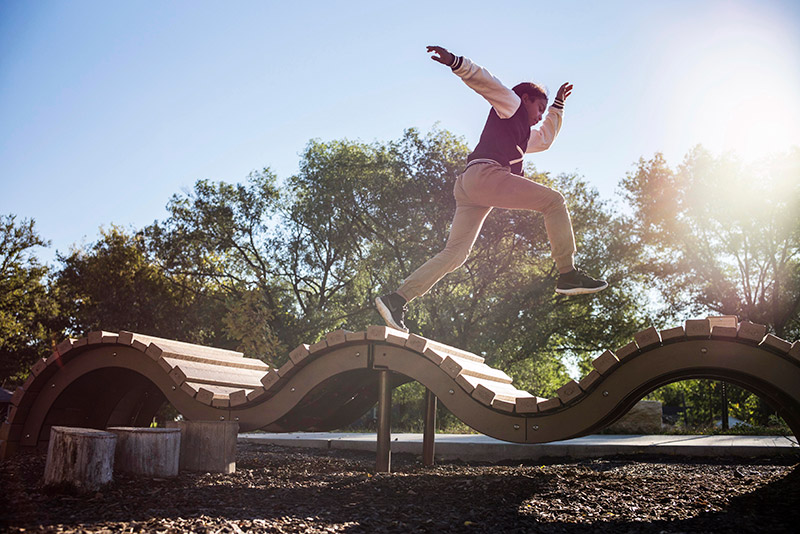 Photo of a kid jumping on a bridge in a playground