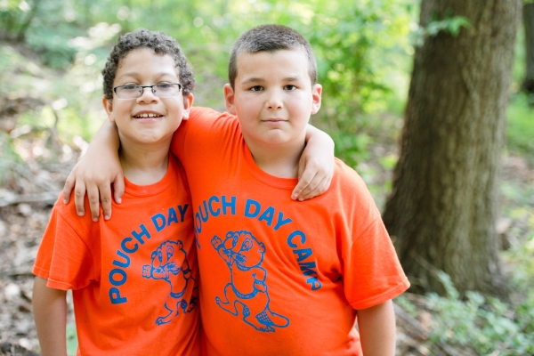 Two campers with their arms around each other smile for the camera at Pouch Camp on Staten Island, NY.