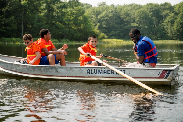 Camp couselors and campers take off on a rowboat ride on the lake at Pouch Camp on Staten Island, NY.