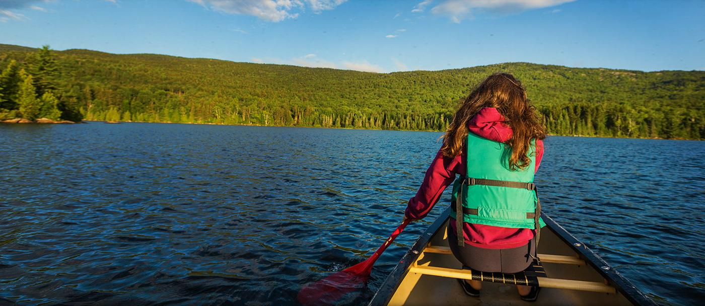 A teenage girl paddles in the bow of a canoe on Bald Mountain Pond.