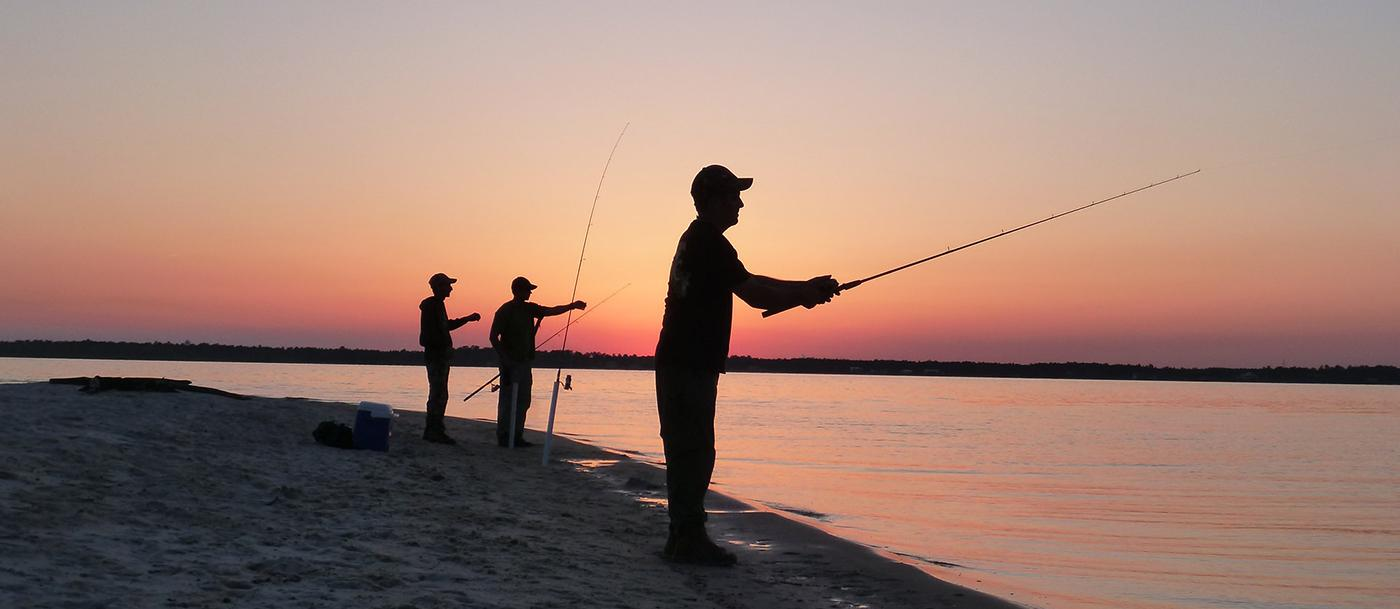 Three silhoutted people fish on a beach