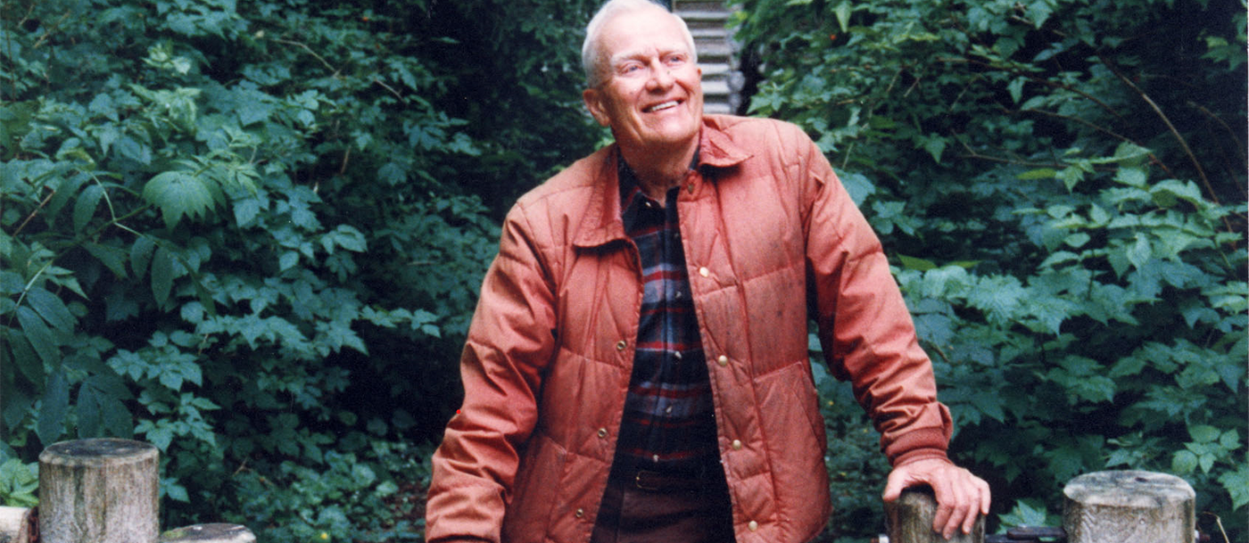Jim Ellis stands at a log fence in front of a cabin in the woods outside of Seattle, Washington.
