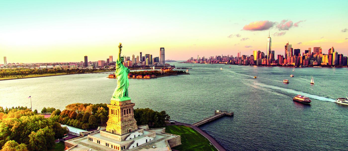 Aerial image of the Statue of Liberty in the foreground, with Manhattan and Brooklyn skylines behind