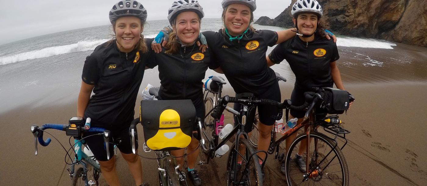 Four cyclists smile with their bikes on a beach
