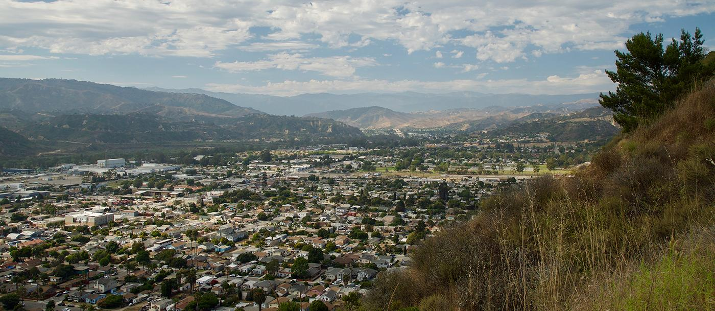 A neighborhood fills a valley in a photo taken from a hillside above it