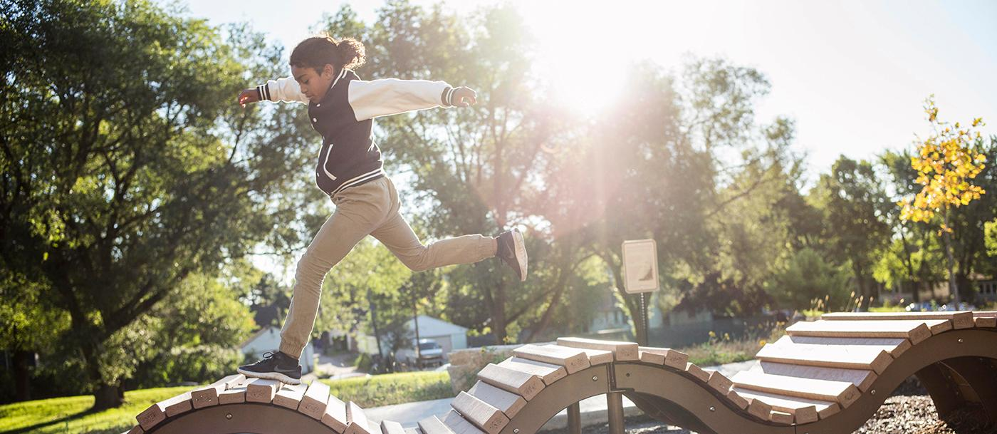 A boy runs on an undulating play structure