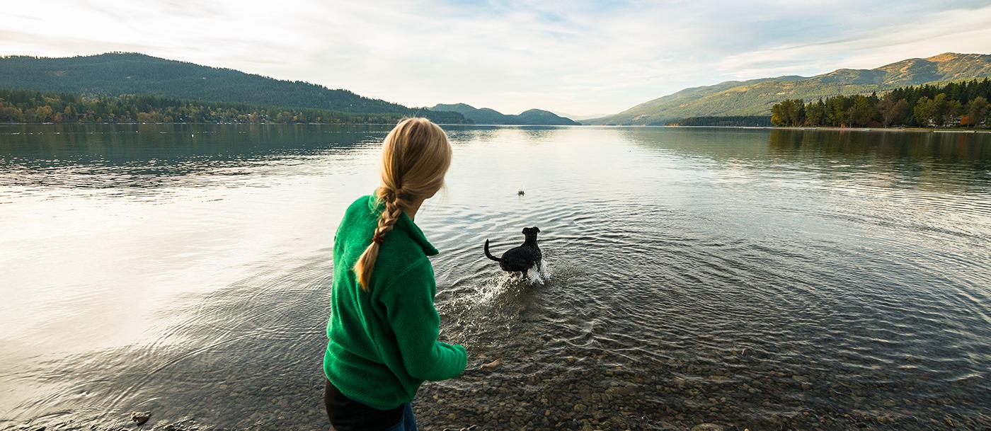 A woman plays fetch with her dog at Whitefish Lake in the Haskill Basin in Whitefish, MT