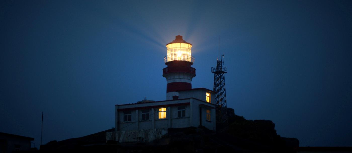 A lighthouse shining in the night.