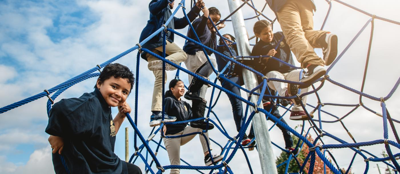 Kids play on a climbing structure