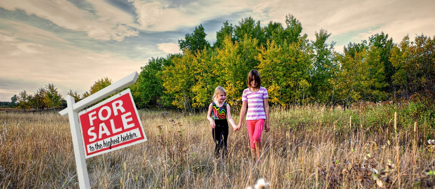 Two girls walk through a field near the Story Mill Connecter Trail
