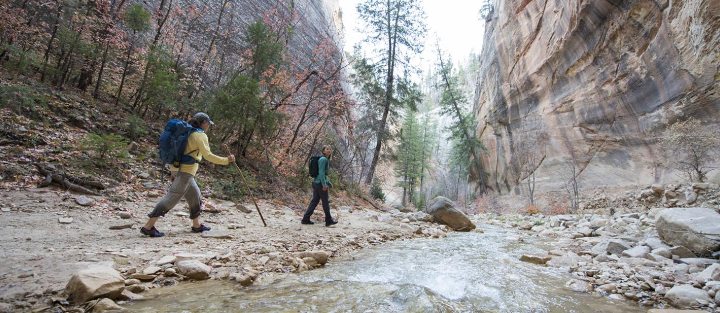 Two hikers explore the Zion Narrows trail on the Simon Gulch Property in Zion National Park, UT.