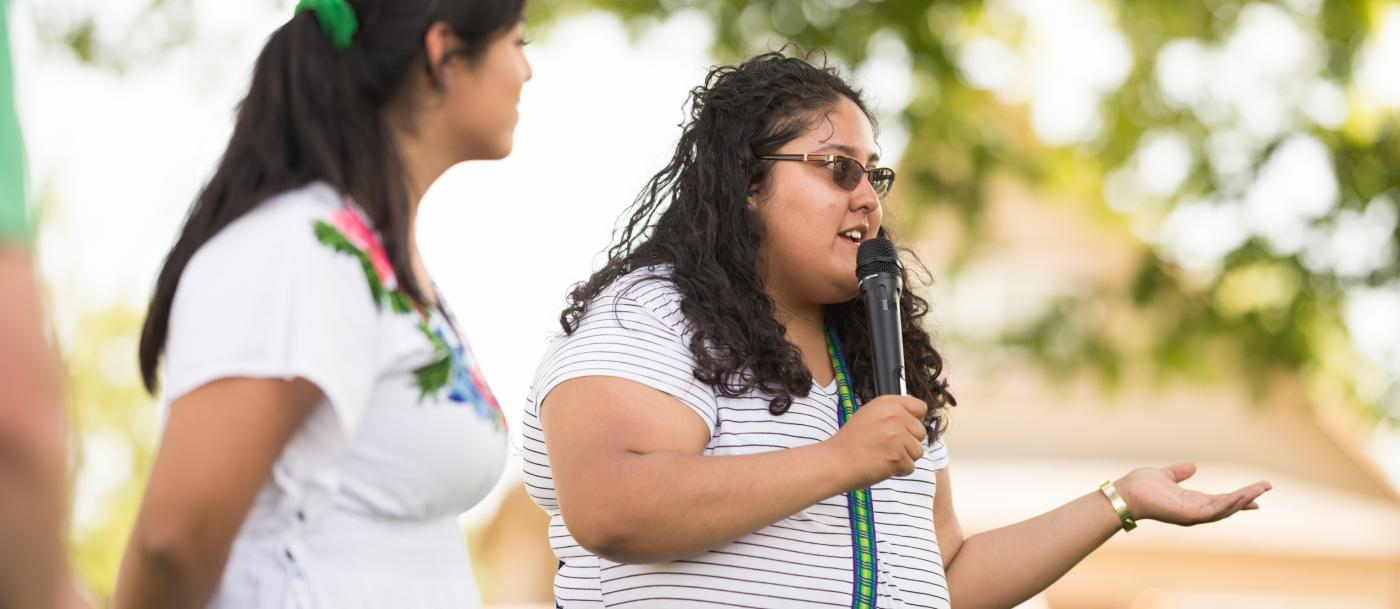 Two young women address a crowd at a park