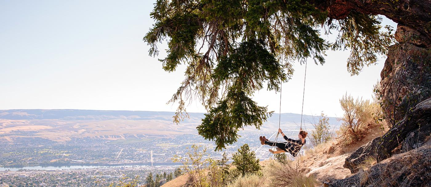 A woman on a swing on the Saddle Rock trail in Wenatchee, Washington.