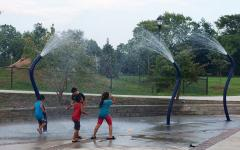 Photo of kids playing in a water splash pad in a park  Photo of kids playing in a water splash pad in a park