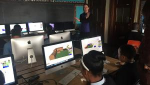 Photo of a classroom with a teacher, students and computers