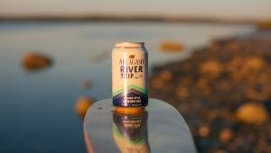 A can of Allagash River Trip beer balances on a canoe paddle with a stream in the background