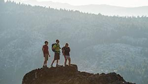 Three hikers stop atop a rock vista to admire the view under the afternoon light, on Donner Summit, CA