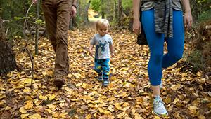 A toddler boy walking with his family at Walden Woods.
