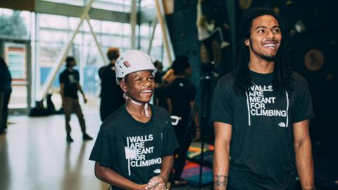 A teenage boy and a young man smile for the camera at an indoor rock climbing gym