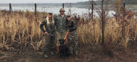Three young people wearing camouflage with a dog