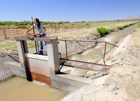 A woman works on an acequia irrigation ditch in New Mexico