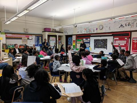 Photo of children and a teacher in a class room
