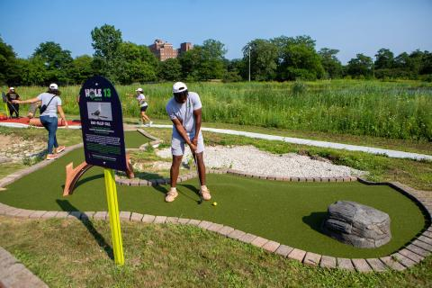 A teenager golfs at the Douglass 18 mini golf course in Chicago