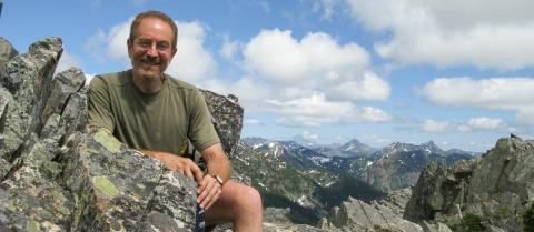 Dr. Howard Frumkin wears a green shirt and sits on lichen-covered rocks in front of a mountain vista