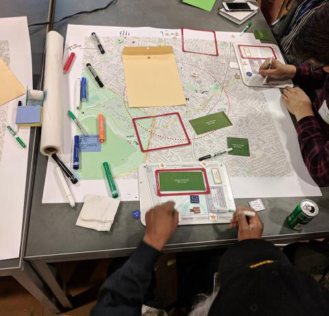 Photo of kids planning with a map, phones, laptops