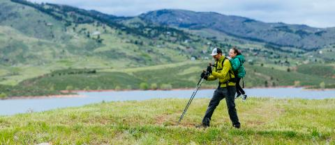 A man carries a woman in a backpack on a hike through a green field