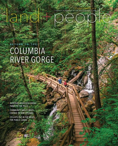 Magazine cover with image of two people crossing a forest bridge