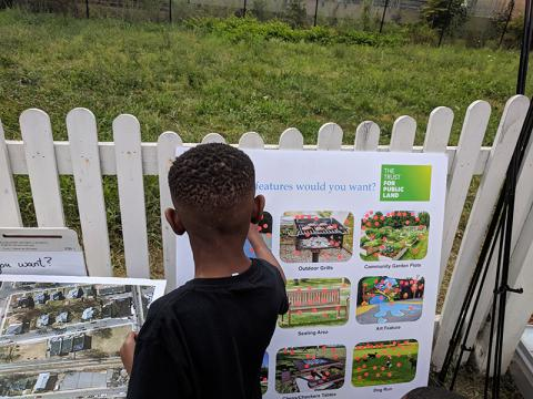 Photo of a kid standing in front of a white picket fence with Trust for Public Land project images on a poster