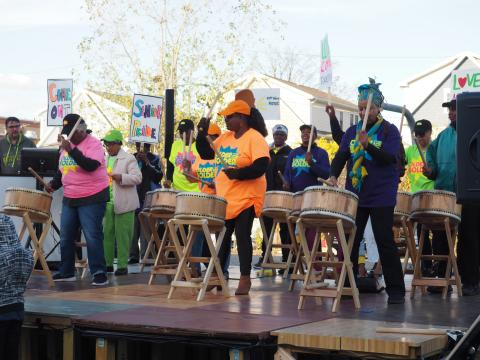 A group of senior citizens on stage in bright t-shirts playing drums with stucks