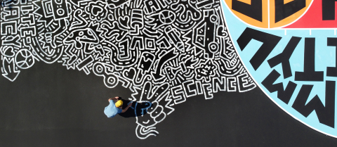 Aerial view of Timothy Goodman painting a white mural on black asphalt