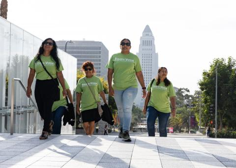 Four women in sunglasses climb the steps outside Los Angeles City Hall