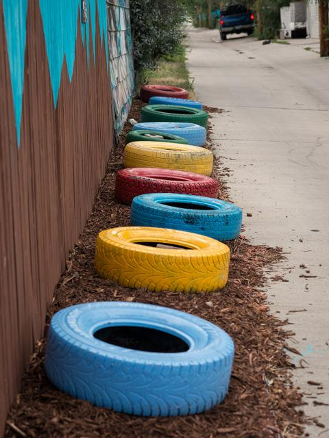 Photo of painted tires along a fence