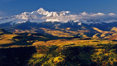 A snowy Wilson Peak rises above autumn forests near Telluride, Colorado